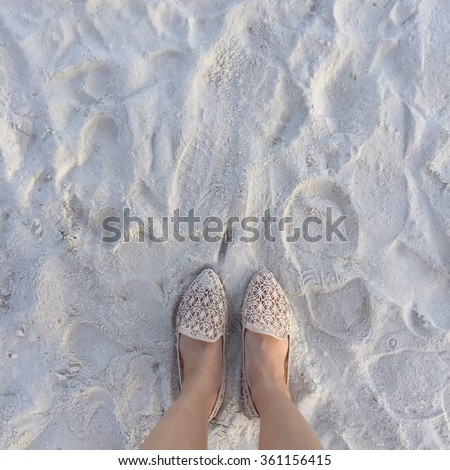 Selfie of woman feet wearing flip flops on a beach, vintage process - stock photo