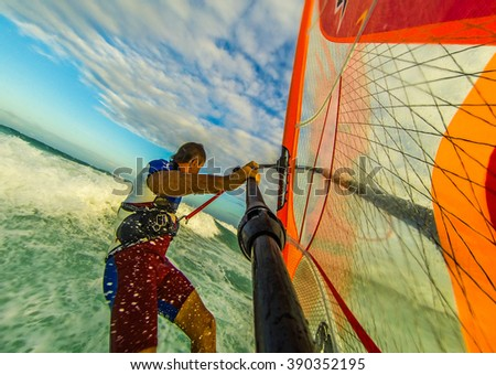 Selfie photo of windsurfing riding on colored sail - stock photo
