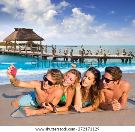 Selfie photo of young friends group in a tropical beach lying on sand - stock photo