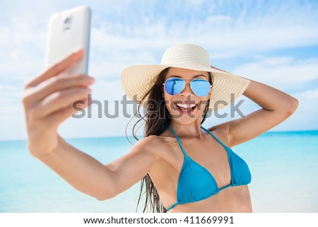 Selfie smartphone girl taking mobile phone photo on beach vacation during summer travel holidays. Sexy young bikini woman wearing fashion mirrored aviator sunglasses posing for camera having fun. - stock photo