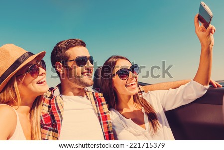 Selfie! Three young happy people enjoying road trip in convertible and making selfie - stock photo