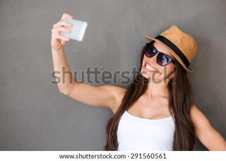 Selfie time. Joyful young women making selfie by her smart phone and smiling while standing against grey background - stock photo
