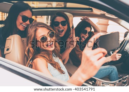 Selfie time! Side view of four beautiful young cheerful women making selfie and smiling while sitting in car together - stock photo