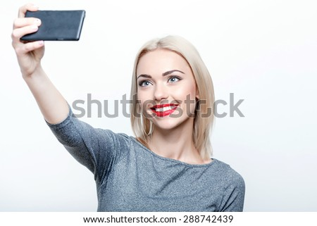 Selfie time. Young smiling blond-haired lady doing selfie on isolated white background - stock photo