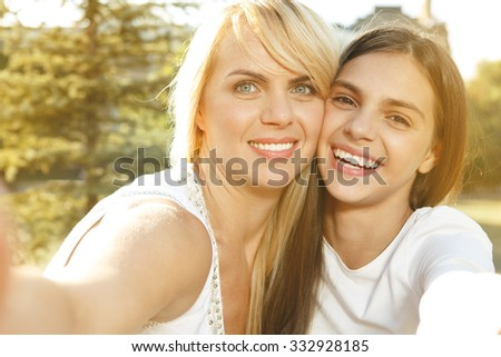 Selfie together. Happy smiling mother and her teenage daughter taking a selfie picture together - stock photo