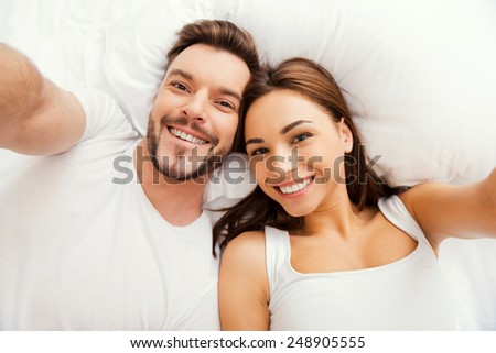 Selfie! Top view of beautiful young loving couple lying in bed and making selfie - stock photo