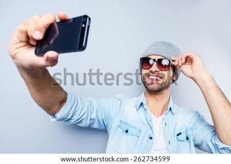 Selfie! Top view of handsome young man in hat and sunglasses making selfie and smiling while standing against grey background - stock photo