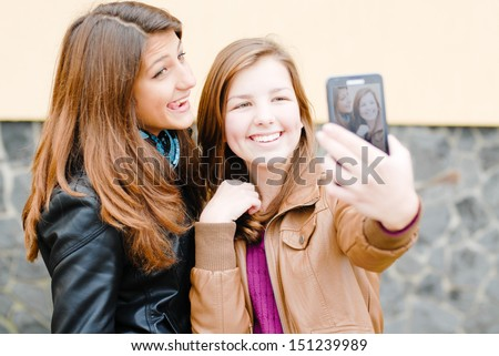 selfshot or selfy portrait: Two teen girls taking picture of ...