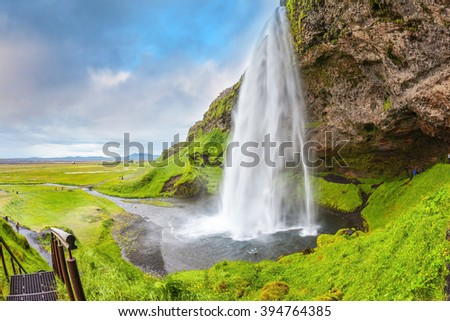 Seljalandsfoss waterfall in July. Large rainbow decorates a drop of water. The warm July day in Iceland - stock photo