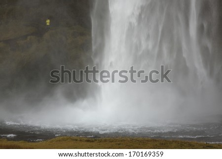 Seljalandsfoss waterfall with tourist in yellow jacket giving scale - stock photo