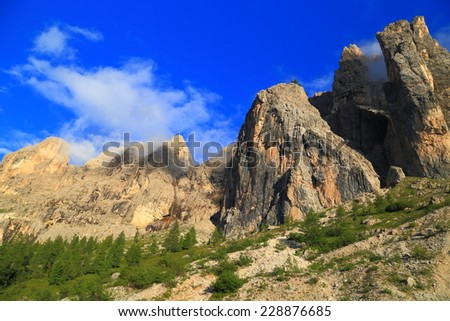 Sella massif walls above the green vegetation in Lasties Valley, Dolomite Alps, Italy - stock photo