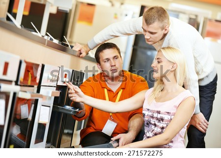 Seller assistant demonstrating cooker stove to young family in home appliance shopping mall supermarket - stock photo