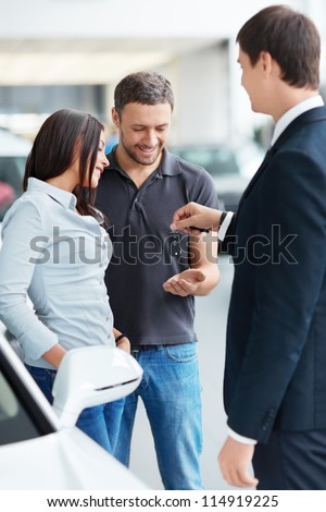 Seller gives the keys a couple in the showroom - stock photo
