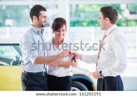 Seller handing car keys to a happy couple in a salon - stock photo