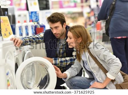 Seller helping customer with choosing washing machine - stock photo