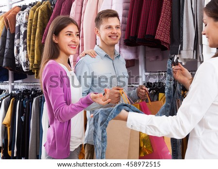 Seller in a clothing store advises a young couple