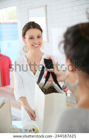 Seller in clothing store giving bag to customer - stock photo