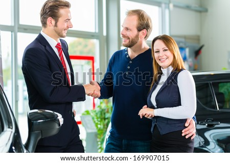 Seller or car salesman and clients or customers in car dealership presenting the interior decoration of new and used cars in the showroom - stock photo