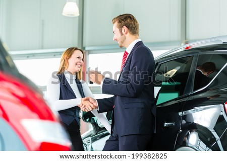 Seller or car salesman and customer in dealership, they shaking hands, hands over the car keys and seal the purchase of the auto or new car - stock photo