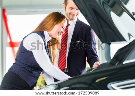 Seller or car salesman and female client or customer in car dealership presenting the engine performance of new and used cars in the showroom, the woman looks under the hood - stock photo