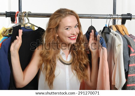 Seller shows clothes hung on hangers and waits for customers against a light background - stock photo