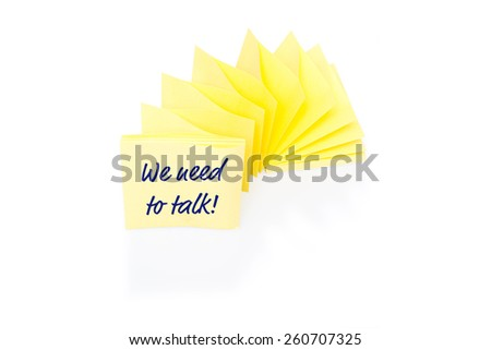 Sellow sticky note with message - We need to talk - on block with shadow and reflection on white background - stock photo