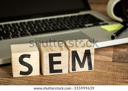 SEM (Search Engine Marketing) written on a wooden cube in a office desk  - stock photo