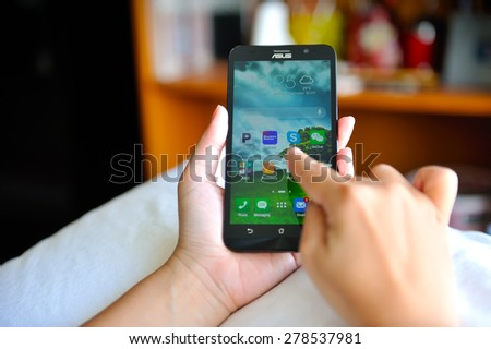 SEMBAWANG, SINGAPORE - MAY 17, 2015: Woman holding brand new Asus Zenfone 2. Social media are trending and both business as consumer are using it for information sharing and networking.  - stock photo