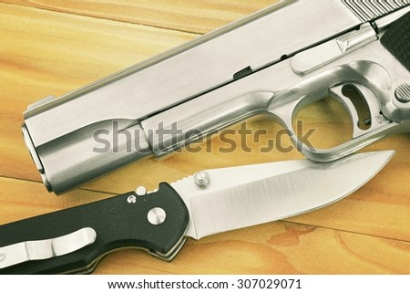 Semi-automatic handgun and tactical knife on wooden background, .45 pistol. (Vintage Style Color) - stock photo