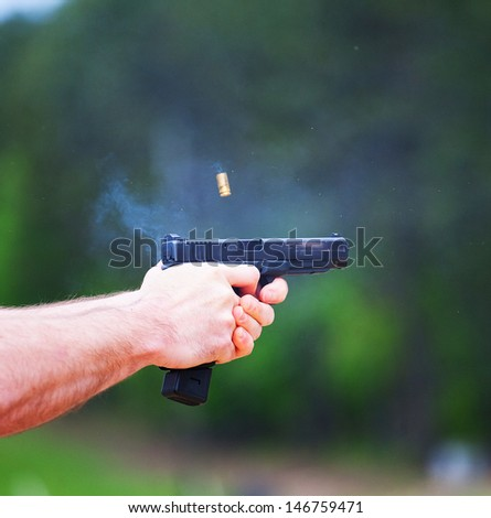 Semi automatic handgun being shot with brass in the air - stock photo