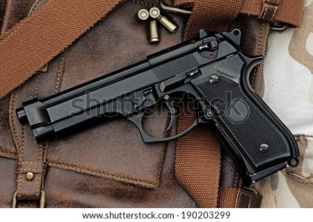 Semi-automatic handgun lying over a Leather handbag, 9mm pistol, Process HDR detail - stock photo