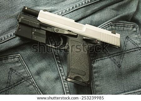 Semi-automatic handgun on blue jeans background, 9mm pistol. Process HDR detail. - stock photo