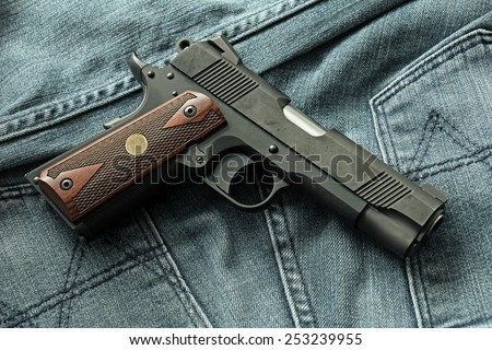 Semi-automatic handgun on blue jeans background, .45 pistol. - stock photo