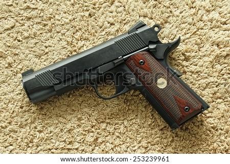 Semi-automatic handgun on carpet background, .45 pistol, 1911 model. - stock photo