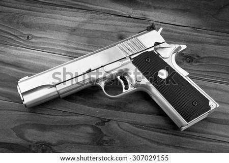 Semi-automatic handgun on grey wooden background, .45 pistol. Guns. (Black & White) - stock photo