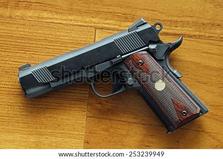 Semi-automatic handgun on wooden background, .45 pistol, 1911 model. - stock photo