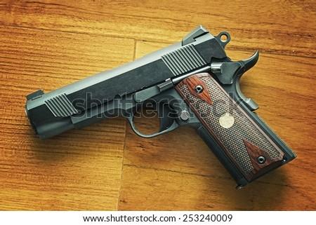 Semi-automatic handgun on wooden background, .45 pistol, 1911 model. Process HDR detail. - stock photo