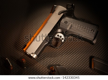 Semi automatic handgun that in on a textured gray background - stock photo