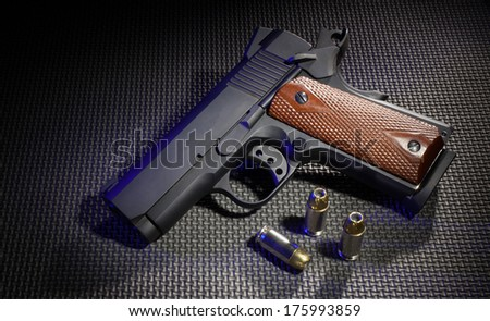 Semi automatic handgun with blue lighting and three cartridges - stock photo