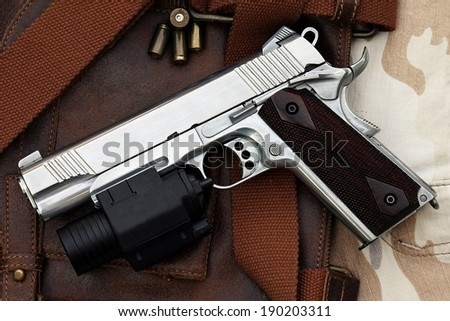 Semi-automatic handgun with tactical flashlight lying over a Leather handbag,  45 pistol - stock photo