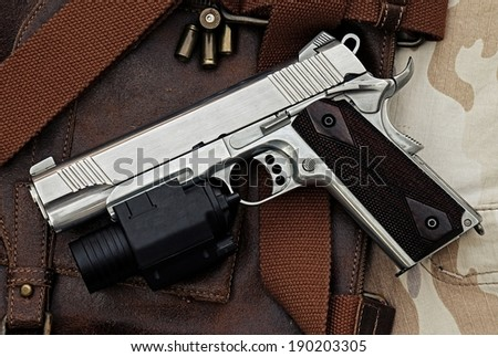 Semi-automatic handgun with tactical flashlight lying over a Leather handbag,  45 pistol,  Process HDR detail - stock photo