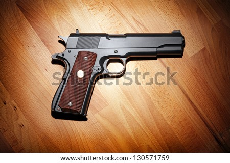 Semi-automatic M1911 Mark IV Series 80 .45 caliber pistol on the wooden table. - stock photo