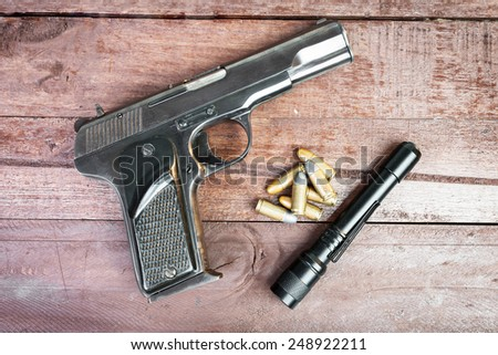Semi-automatic 9mm gun and and tactical flashlight lying over on wooden background. - stock photo