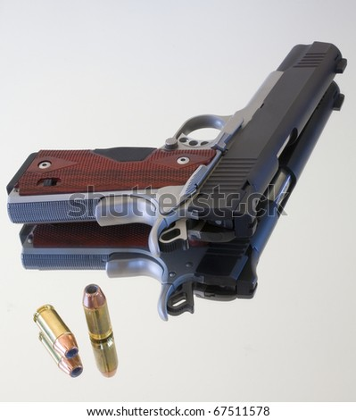 Semi automatic pistol and bullets that are on a mirror - stock photo