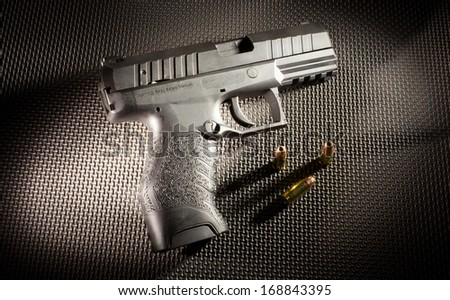 Semi automatic polymer handgun with some ammunition - stock photo
