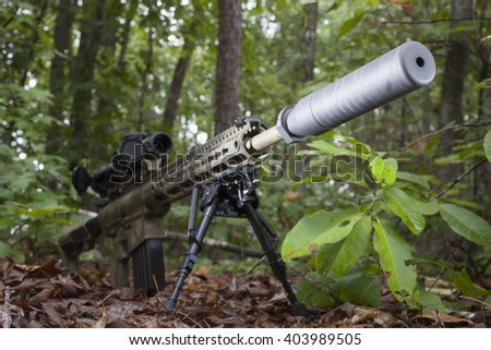 Semi automatic rifle with camouflage and a suppressor on the end - stock photo