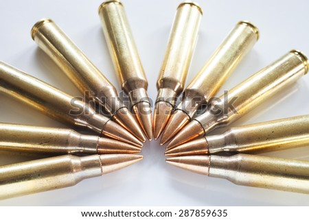 Semi circle of cartridges on white that have bullets with a steel core - stock photo