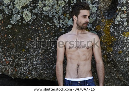 Semi dressed young man by rocks, looking away - stock photo