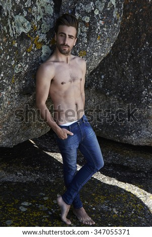 Semi dressed young man in jeans on rocks - stock photo