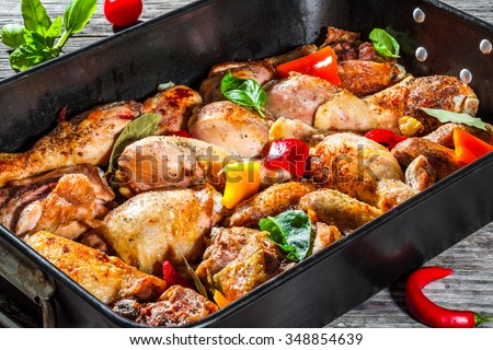 semi-fried chicken meat with colorful pieces of peppers basil leaves and spices in the baking dish preparing for roast in the oven the festive dinner view from above